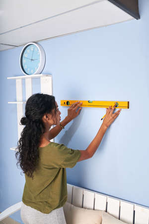 Young woman using construction level to measure the wall