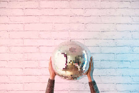 Close-up shot of female hands holding disco ball, white brick wall on background, copy space