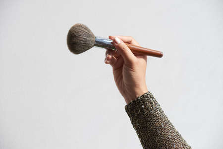 Close-up shot of unrecognizable make-up artist holding powder brush in hand, isolated on white background