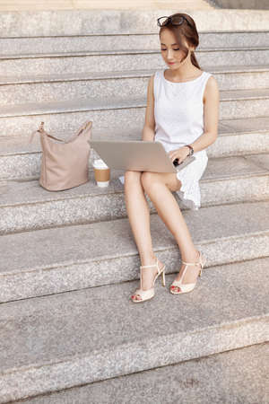 Elegant young woman sitting on stairs and reading e-mail on her laptop