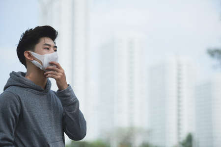 Jeune homme vietnamien dans une ville polluée recouverte de smog épais