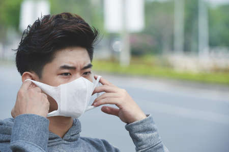 Face of Asian young man wearing face mask Stockfoto