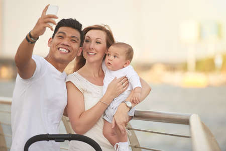 Mixed-race family of three taking selfie on smartphone while standing at riverwalk, cute baby looking at device with curiosity