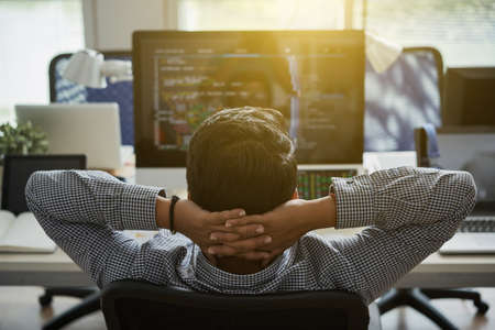 Programmer leaning back in his chair and looking at his code on computer screen Stock Photo
