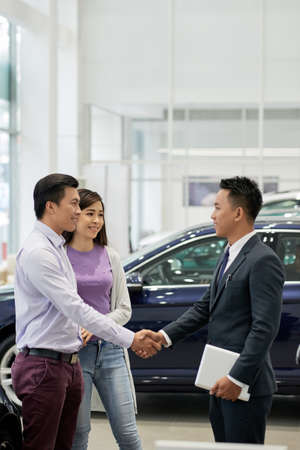 Couple telling thank you to car dealership assistant