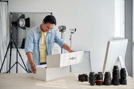 彼が受け取った新しいレンズを持つアジアの写真家のオープニングボックス 写真素材