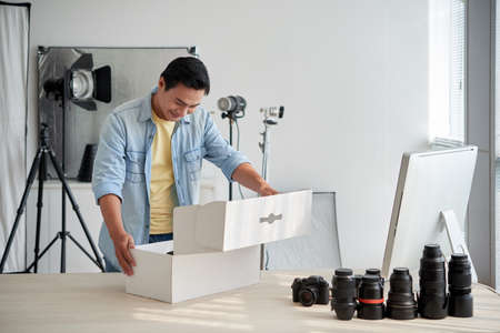 Asian photographer opening box with new lenses he received