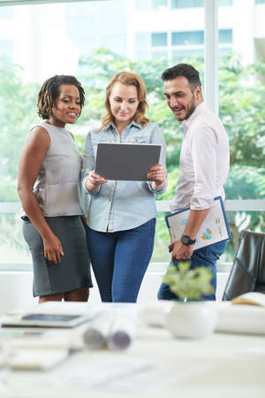 Multi-ethnic group of colleagues standing at spacious open plan office and analyzing results of accomplished work with help of digital tablet