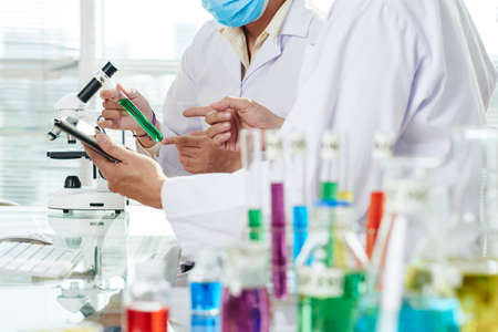 Close-up shot of unrecognizable chemists wearing white coats examining content of test tube and taking necessary notes with help of digital tablet while carrying out experiment.