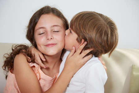Boy kissing his older sister on cheeck