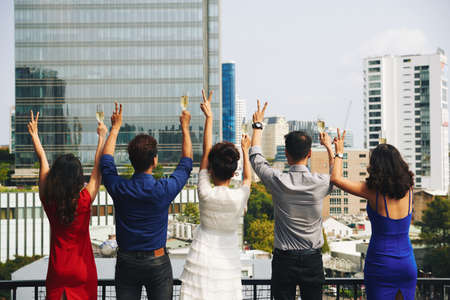 Rear view of partying people standing on rooftop and showing victory gesture