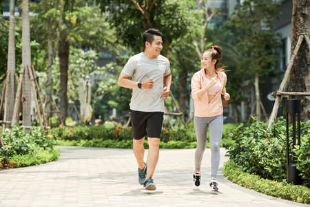 Vietnamese man and woman jogging together in the park