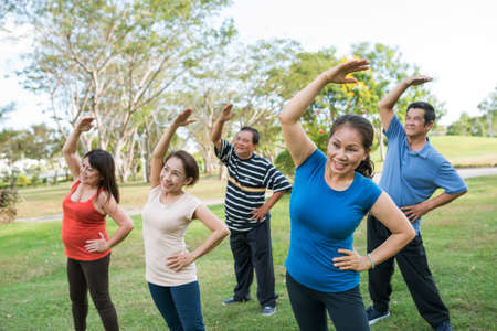 Vietnamese sporty woman exercising with group of senior people