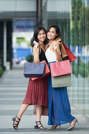Joyful young Asian woman with many paper-bags and credit cards standing outdoors Stock Photo