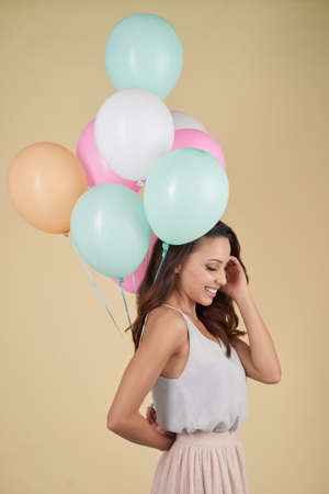 Smiling attractive young woman in tender outfit touching hair while being embarrassed, pretty girl holding heap of balloons