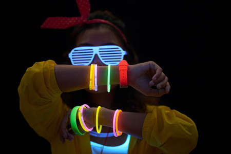 Cheerful young woman with neon bracelets in dark room 版權商用圖片 - 102758378