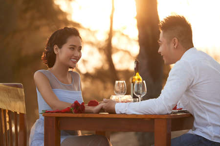 Loving Asian couple holding hands and enjoying each others company while having romantic dinner at sunset on tropical beach