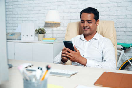 Confident Indian businessman sitting at office desk and text messaging on cell phone Stock Photo