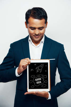 Indian businessman showing Good Idea drawing on tablet computer screen Stock Photo