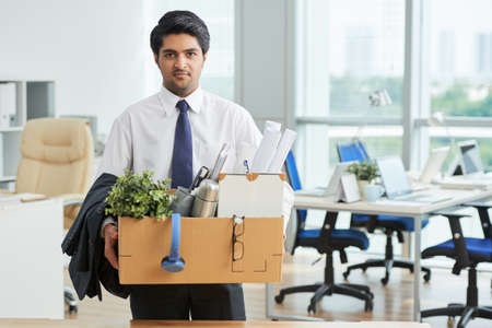 Portrait of Indian businessman with box with office stuff standing at office Stock Photo