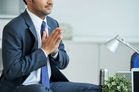 Close-up of businessman meditating on his workplace at office