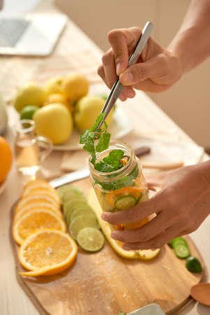 Close-up shot of creative food blogger applying ingredients for citrus infused water in container with tweezers Stockfoto