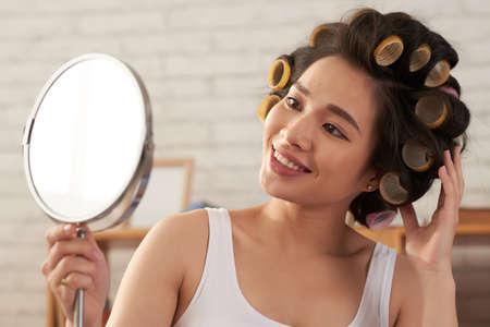 Głowa i ramiona portret pięknej azjatyckiej kobiety noszącej lokówki, patrząc w lustro z szerokim uśmiechem, wnętrze domu na tle