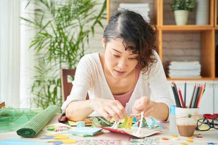 Concentrated middle-aged woman focused on making greeting card for her daughter while sitting at modern living room illuminated with sunbeams, portrait shot Stock Photo