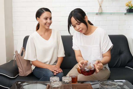 Young happy female looking at her friend pouring tea for her while both sitting on sofa
