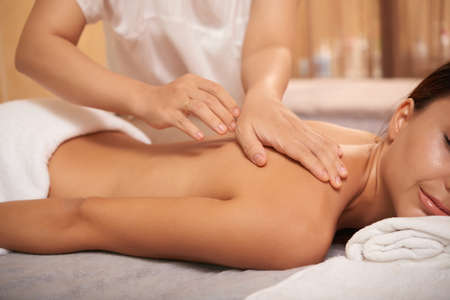 Masseuse hands touching back of relaxed client during massage in spa salon Stock Photo
