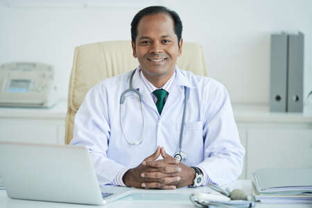 Portrait of smiling Indian male doctor sitting at his workplace