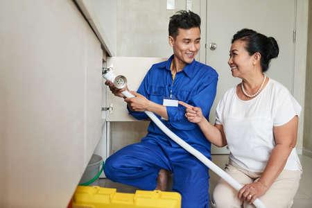 Handyman helping senior woman in kitchen