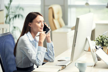 Beautiful professional young woman sitting at modern working table in office and having phone call Stock Photo