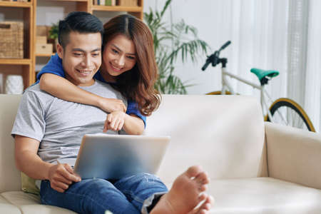 Beautiful Asian young couple on sofa at home surfing laptop together and smiling happily Stock Photo