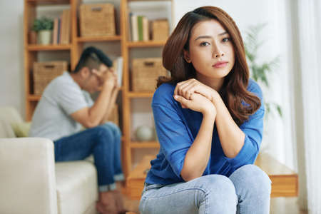 Beautiful and sad Asian woman sitting alone with man in conflict on background and looking at camera