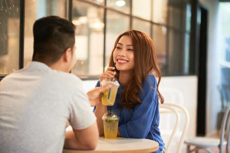 Back view of man sitting with charming Asian woman at table in cafeteria sharing with cool drinks and laughing 版權商用圖片