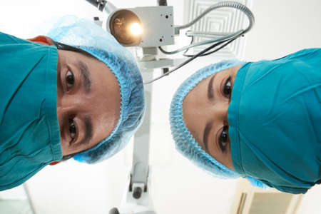 From below shot of Asian man and woman in surgeon masks and caps looking at camera working in operating room