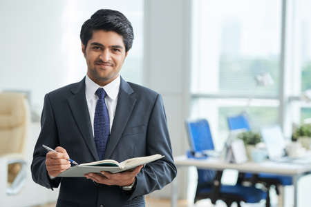 Handsome young businessman with planner