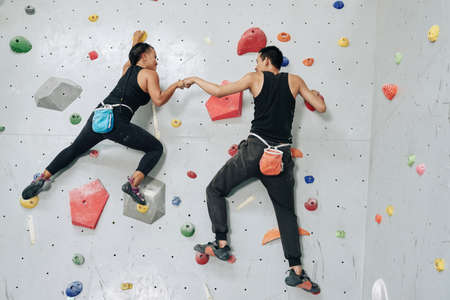 Back view man and woman working out in team and hitting hands while hanging on wall in bouldering center Stockfoto