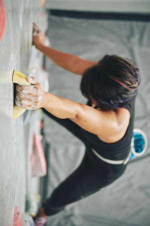 From above of anonymous sportive woman with hands in chalk training in gym and climbing wall with artificial boulders Stock Photo