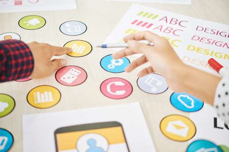 Crop shot of coworking man and woman choosing colorful icon for mobile application while creating new design