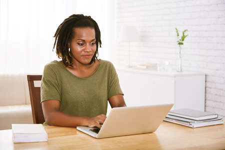 Attractive woman working on laptop at table in her living room
