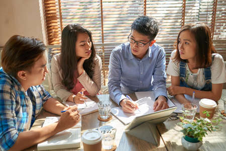 Teacher of English explaining topic to group of students Stock Photo