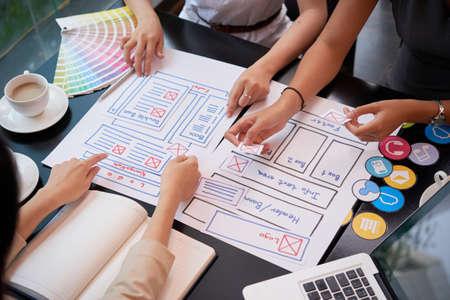 Diseñadores de UI que crean un prototipo de sitio web en una reunión, vista desde arriba Foto de archivo