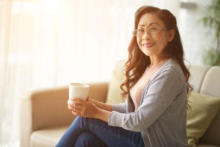 Pretty senior Asian woman resting on sofa with big mug of hot chocolate Stock Photo