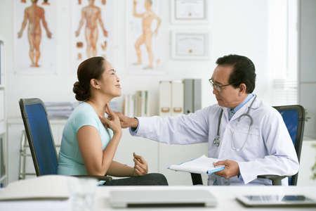 Doctor palpando la garganta de la mujer mayor para hacer un diagnóstico Foto de archivo