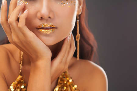 Crop view of relaxed tanned female with bright sparkling golden glitter on lips and cheekbones standing over grey studio background with slightly open mouth and touching face.