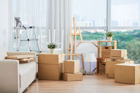 Spacious interior with large packed carton boxed for moving on floor with sofa and drawing easels nearby at large glass wall on sunny day 写真素材