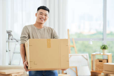 Happy cheerful ethnic male in casual clothes carrying cardboard box and looking at camera on moving day with cartons and drawing easels on blurred background Stock fotó
