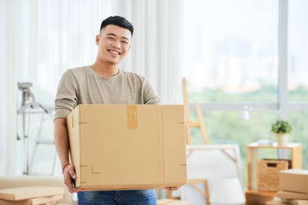 Heureux homme ethnique gai dans des vêtements décontractés transportant une boîte en carton et regardant la caméra le jour du déménagement avec des cartons et des chevalets de dessin sur fond flou